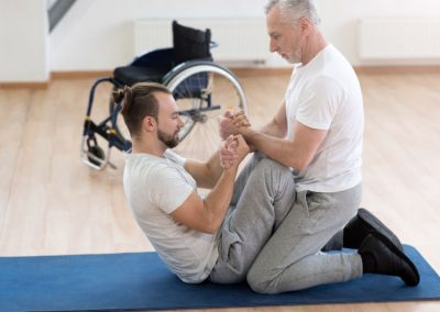 Developing muscles and limbs. Helpful athletic powerful general practitioner stretching the handicapped and assisting him while holding arms of the patient