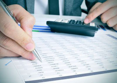 closeup of a young businessman checking accounts with a calculator in his office
